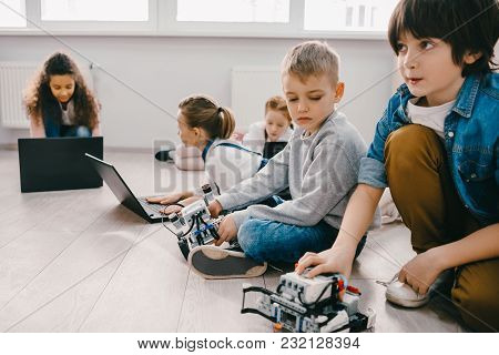 Focused Kids Programming Robots With Laptops While Sitting On Floor, Stem Education Concept