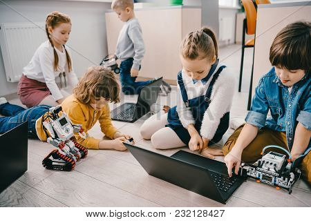 Kids Programming Diy Robots With Laptops While Sitting On Floor, Stem Education Concept