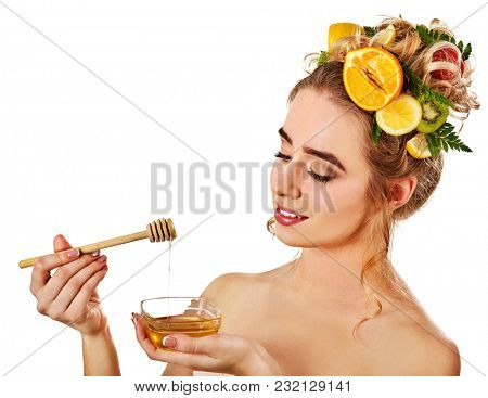 Honey facial mask with fresh fruits for hair and skin on blond woman head. Girl with beautiful face hold honeycombs for homemade organic skin and hair therapy. Acne Removal.