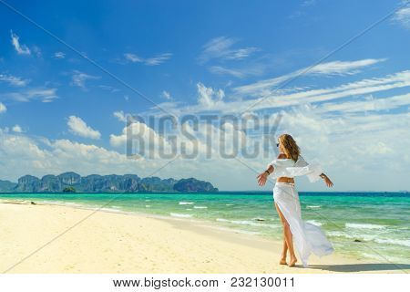 Rear view of a young woman on the sand near the indian  ocean