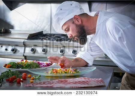Chef garnishing flower in ceviche dish with hands at stainless steel kitchen