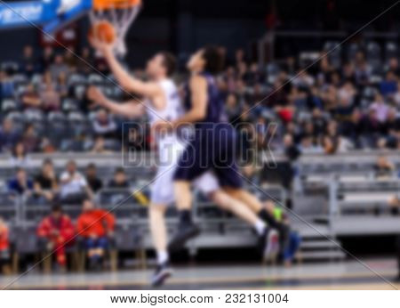 blurred basketball players in action on court