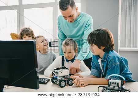 Teacher Working With Teen Students On Diy Robot On Stem Education Class