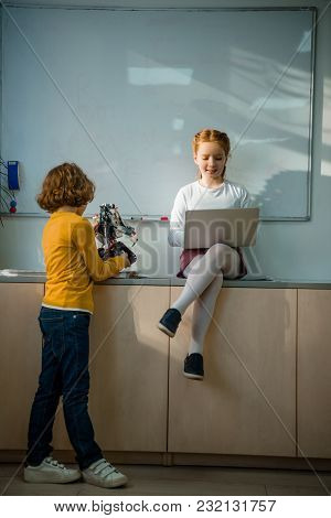 Adorable Little Schoolkids Working Together On Machinery Class