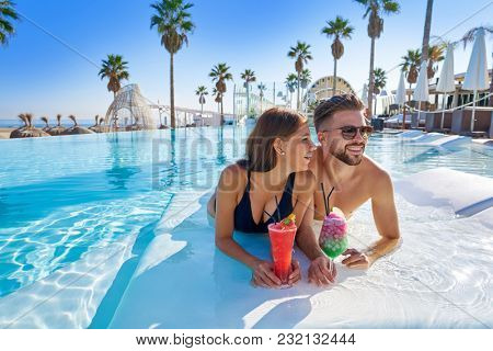 Young tourists couple on infinity pool drinking cocktails at resort on the beach