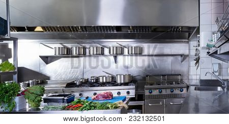 Professional restaurant kitchen in stainless steel with vegetables and meat