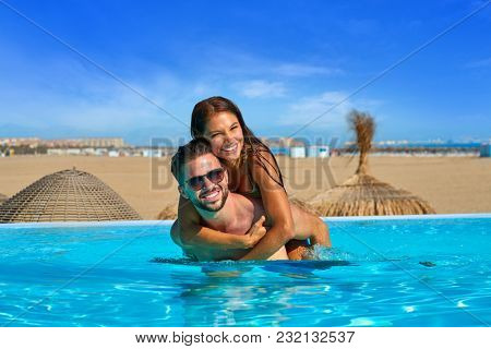 Tourist couple piggyback in infinity pool on a beach resort in summer vacation
