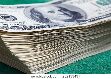 Stack Of One Hundred Dollars Notes On Green Background