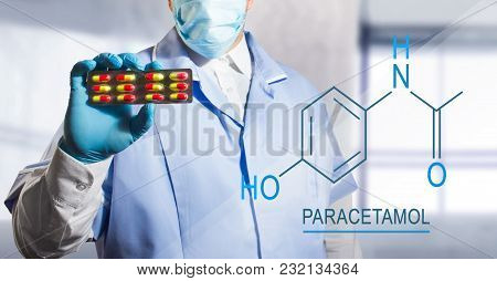 Photo Of A Lab Assistant Holding A Pill Blister With Paracetamol With Chemical Formula Near To Him.