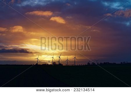 Wind Energy Plants At Sundown With Colorful And Cloudy Sky