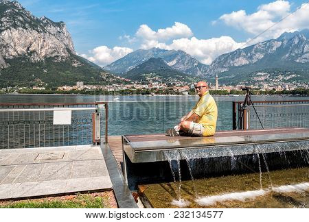 Man Sitting On The Shore Of Como Lake, In Summer Day And Reflects On Life As.