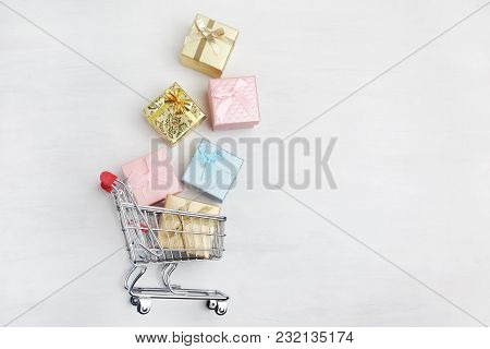 Colorful Gifts Box, Supermarket Shopping Cart On White Wooden Background With Free Space