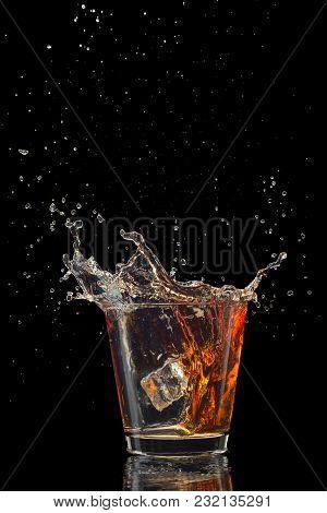 Whiskey Splash Isolated On Black Background Close Up.