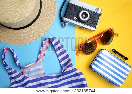Summer Holiday Concept, Travel Concept With Bag, Camera And Hat On Blue And Yellow Background.