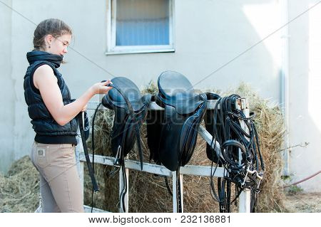 Pretty Teenage Girl Equestrian Cleans Black Leather Horse Saddle And Equipment At Farm On Bright Sun