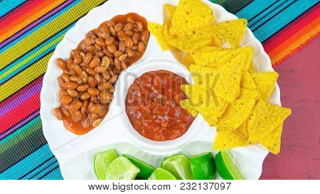 Cinco De Mayo Party Table With Food Platter Including Limes, Corn Chips, Chilli Beans And Salsa On A