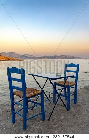 Traditional Greek Tavern Chairs And Table Next To The Sea During Sunset