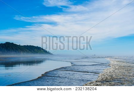 Pacific Northwest Ocean Beach Scene. Distant Mountain Hills Reflecting In Wet Seaside Coastal Sands.