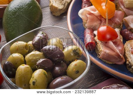 Sharing Mixed Spanish Tapas Starters On Table. Olives, Sandwiches And Avocado.