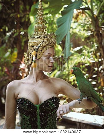 Sensual blonde beauty posing with parrot