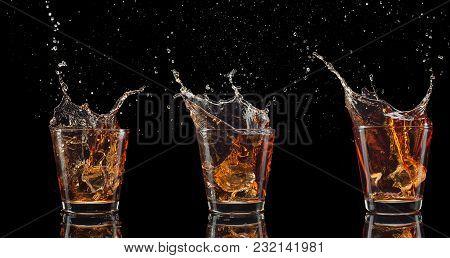 Set Of Whiskey Shots With Splash Isolated On Black Background.