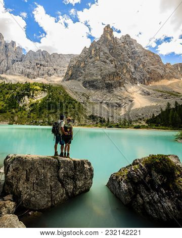 Tourist at Lago di Sorapiss with amazing  turquoise color of water. The mountain lake in Dolomite Alps. Italy