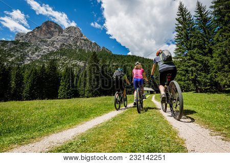 Mountain biking family with bikes on track, Cortina d'Ampezzo, Dolomites, Italy