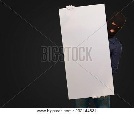 Burglar Man Holding Blank Placard On Black Background