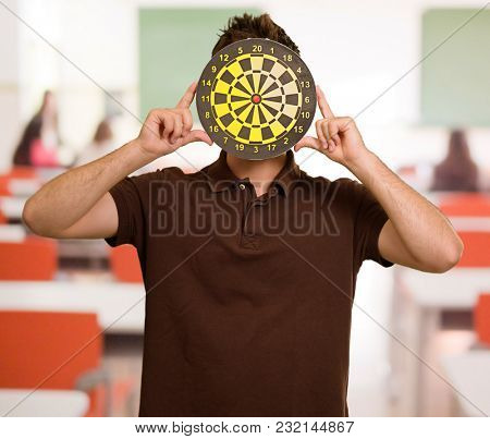 Portrait Of A Man Holding Dartboard, Indoors