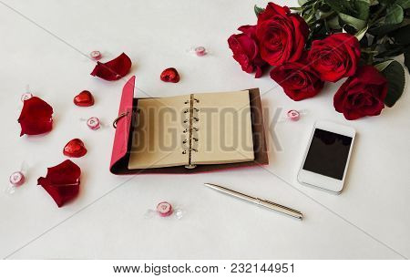 Notebook For Writing With Pen, Candy, Rose Petals And Bouquet Of Red Fragrant Roses On A Wooden Back