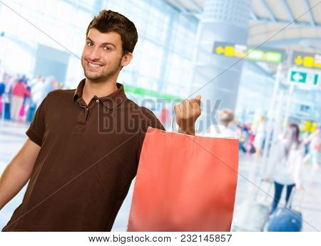 Young Man Holding Shopping Bag, Indoors