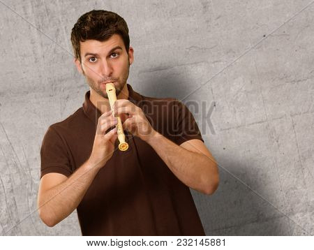 Portrait Of A Young Man Playing Flute On Wall