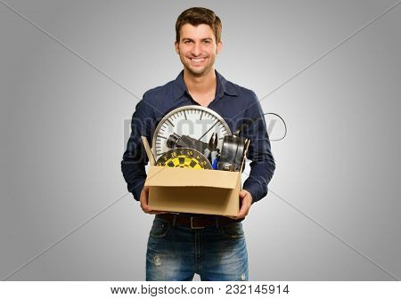 Portrait Of Happy Man Holding Cardboard Box On Grey Background