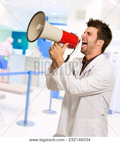 Male Doctor Shouting On Megaphone, Indoors