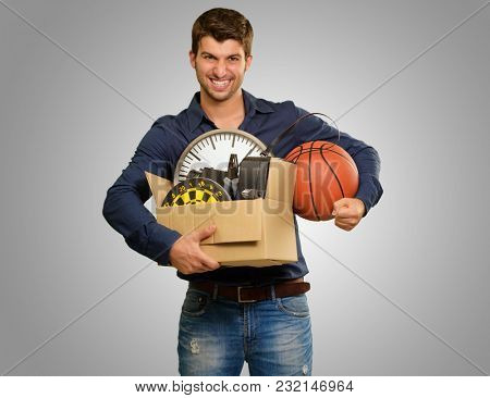 Happy Young Man Holding Cardboxes Gesturing On Grey Background