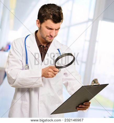 Young Doctor Looking Through Magnifying Glass, Indoors
