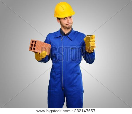 Engineer Holding Brick And Goldbar On Grey Background