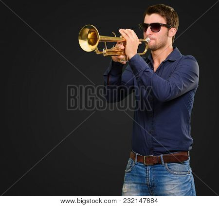 Young Man Holding Trumpet Isolated On Black Background