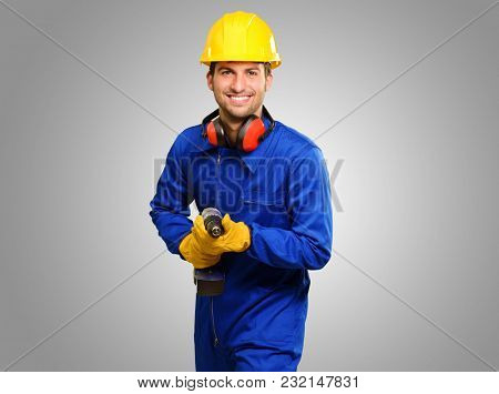 Happy Engineer With Drill Machine Isolated On Grey Background