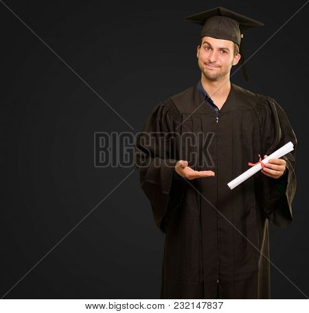 Portrait Of Young Graduation Man Holding Certificate Isolated On Black Background