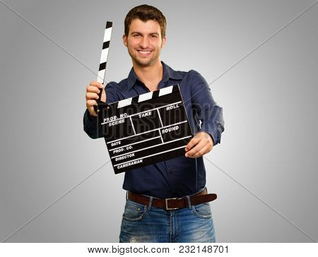 Happy Young Man Holding Clapboard On Grey Background