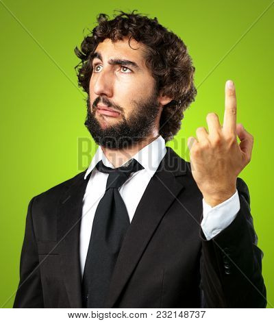 Portrait Of An Unhappy Businessman Pointing Up against a green background