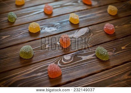 Several Colorful Sweet Marmalades On A Wooden Table
