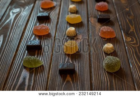 Several Colorful Sweet Marmalades With Chocolate Sweets On A Wooden Table