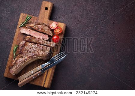 Grilled Cowboy Beef Steak, Herbs And Spices On A Dark Stone Background. Top View With Copy Space For