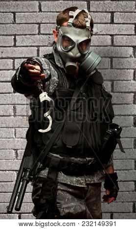 Soldier With  A Gas Mask Holding Handcuffs against a brick wall