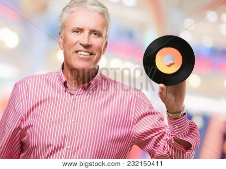 Happy Man Showing Old Vinyl against an abstract background