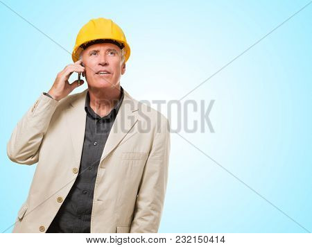 Male Architect Talking On Cell Phone against a blue background