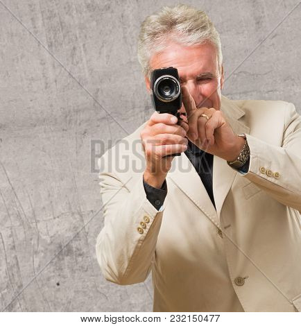 Man Looking Through Camcorder against a concrete background
