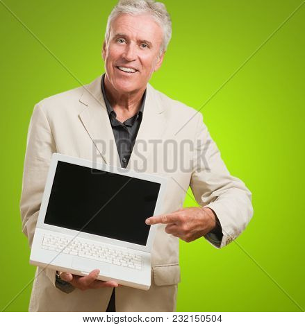 Mature Man With Laptop against a green background